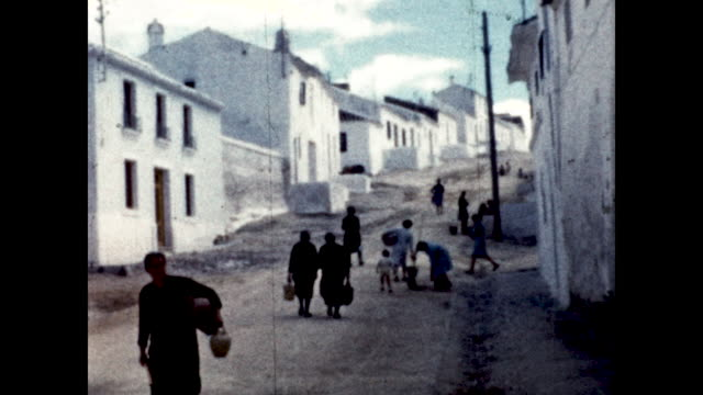 women and children carrying buckets of water uphill white houses on the sides of the dirt road - uphill stock videos & royalty-free footage