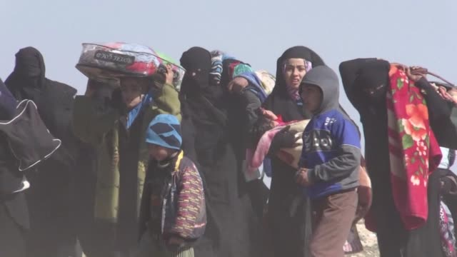 women and children flee the battered islamic state held holdout of baghouz in the eastern syrian province of deir ezzor carrying their belongings... - syrian democratic forces stock videos & royalty-free footage