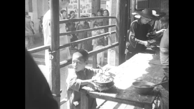 vs women and children standing in line for bowls of rice several people at table with all eating from large bowls with chopsticks / note exact day... - hungrig stock-videos und b-roll-filmmaterial