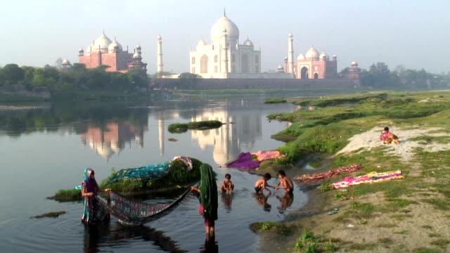Women and children wash saris in the River Yamuna near Taj Mahal in Agra, India.