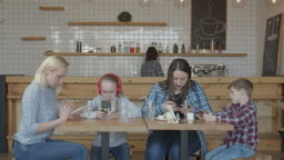 Women and kids using phones sitting at cafe table