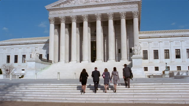 stockvideo's en b-roll-footage met women and men in suits walking up steps to entrance of us supreme court building / washington, dc - gerechtsgebouw
