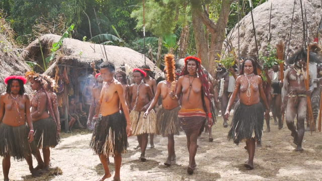 women and men of the dani tribe perform a ritual dance for the safety of their men at war - grashütte stock-videos und b-roll-filmmaterial
