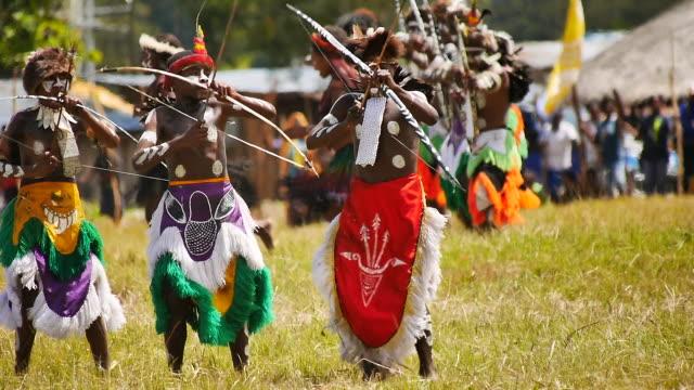 vídeos y material grabado en eventos de stock de women and men of the dani tribe perform a ritual dance for the safety of their men at war - cabaña de paja