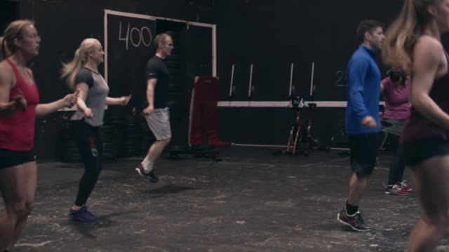 vídeos de stock, filmes e b-roll de women and men skip roping in a gym - calções de corrida