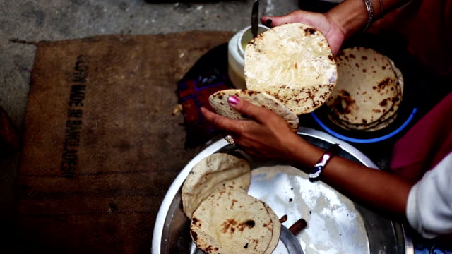 Women Applying butter on chapatti