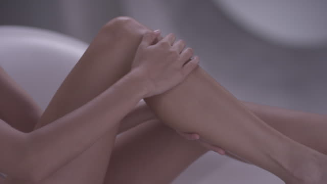 Women applying moisturiser to legs.