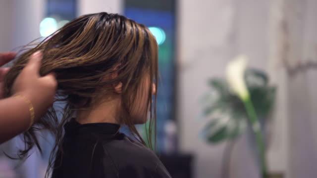 女性は、ヘアサロンで髪を吹いています。 - hair treatment点の映像素材/bロール