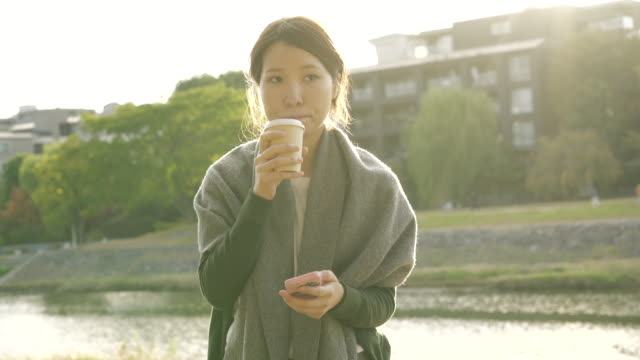women are coffee break and sitting on railing along the river - disposable cup stock videos and b-roll footage