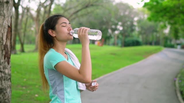 frauen trinken kaltes wasser in den park und die frau, die musik hören. - joggerin stock-videos und b-roll-filmmaterial
