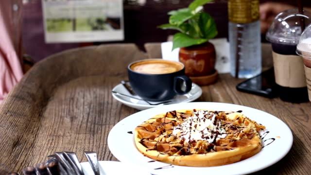 vídeos y material grabado en eventos de stock de las mujeres comen gofres en la cafetería. - waffles