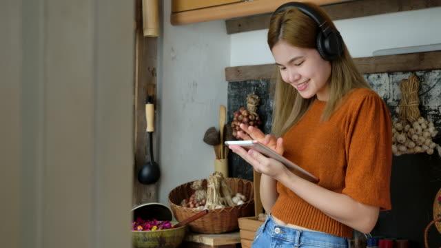 vidéos et rushes de les femmes jouent aux tablettes dans la cuisine. - pavé tactile