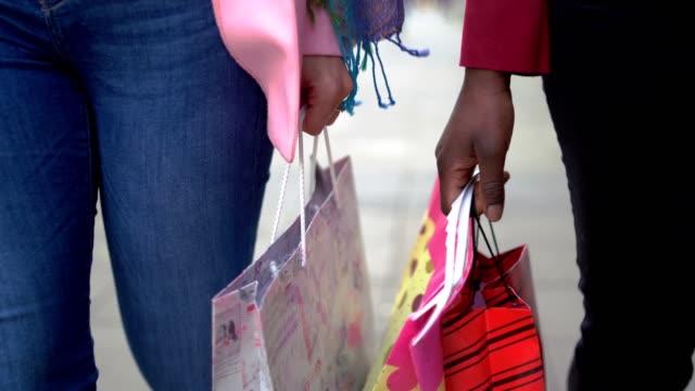 vídeos de stock, filmes e b-roll de as mulheres estão andando na rua cuidando sacos de compras - sacola de compras