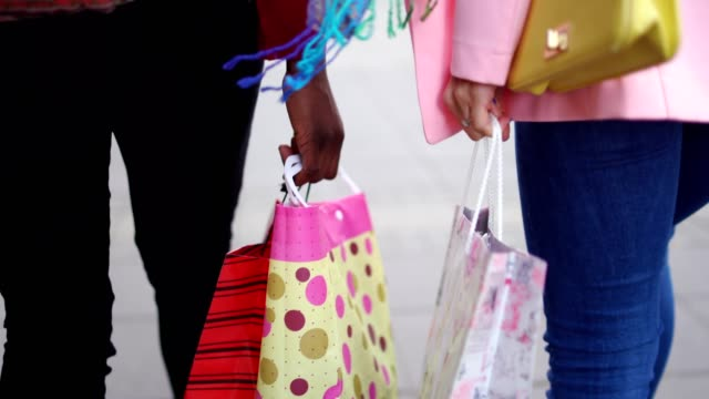 women are walking on the street caring shopping bags - shopping bag stock videos and b-roll footage