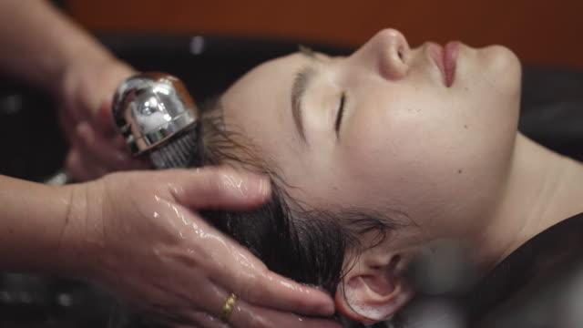 女性は美容室で髪を洗っているし、髪洗うを洗います。 - hair treatment点の映像素材/bロール