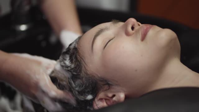 女性は、美容室で髪を洗っています。 - hair treatment点の映像素材/bロール
