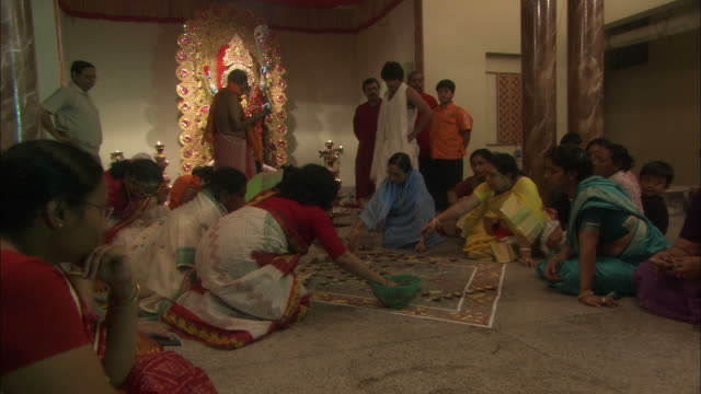 women arrange candles around floor mural as part of offerings to kali goddess for diwali hindu festival of lights available in hd. - routine stock videos & royalty-free footage