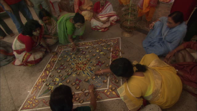 women arrange candles on floor mural as part of offerings to kali goddess for diwali hindu festival of lights available in hd. - routine stock videos & royalty-free footage