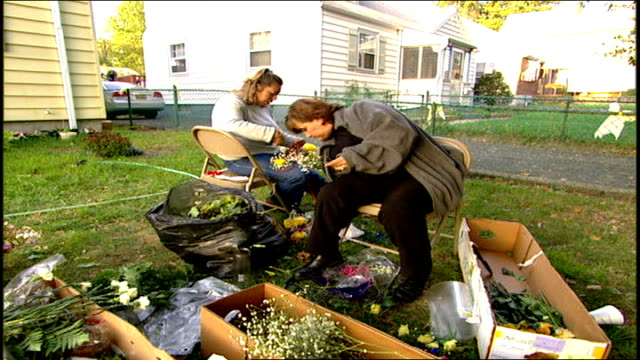 women arranging flowers in vases for 9/11 victims in paterson nj - エディトリアル点の映像素材/bロール