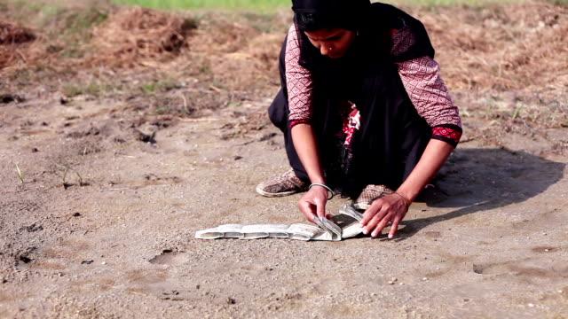 Women arranging money note on ground