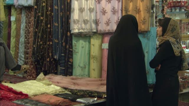 MS TU Women at market stall with large amount of textiles, Shiraz, Iran
