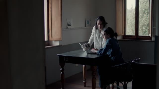 vídeos y material grabado en eventos de stock de women at table, typing on laptop - dentro
