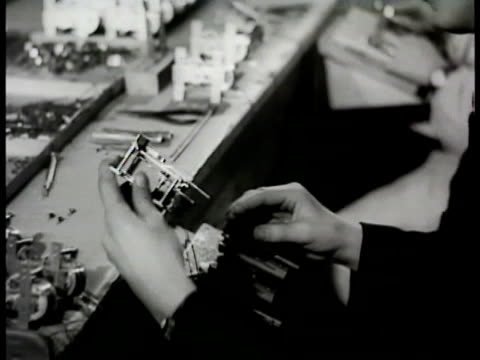 stockvideo's en b-roll-footage met women at tables working on small clock parts movements male in headphones checking swinging clock moving pendulums on wall another male behind moving... - 1948