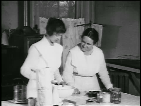 b/w 1920 2 women baking in kitchen (jump cuts) / detroit, michigan / newsreel - stereotypical housewife stock videos and b-roll footage