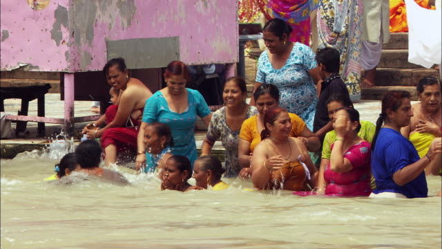 Women bathe and play in the Ganges River in India. Available in HD.