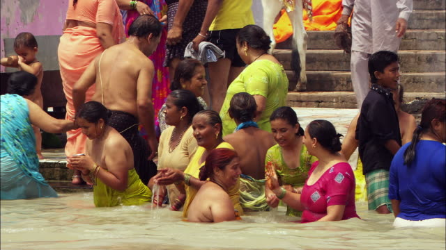 Women bathe in the Ganges River in India. Available in HD.