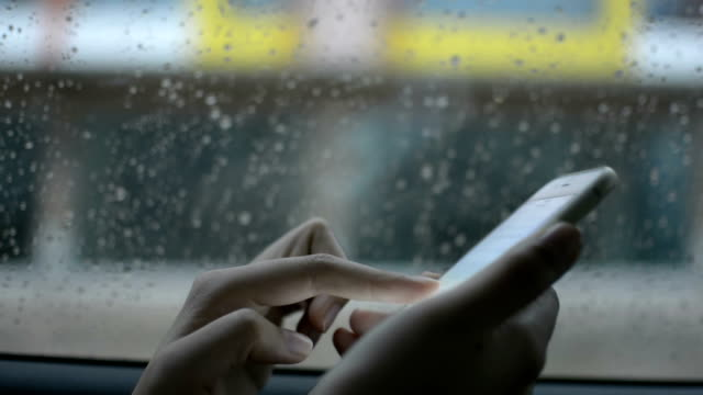 Women behind car window using smartphone in a rainy day.