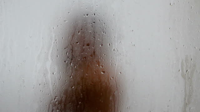 stockvideo's en b-roll-footage met women behind frosted glass shower - matte