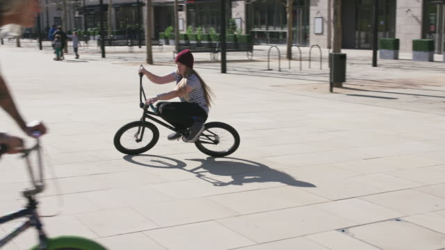 3 women bmx riders cycling and doing tricks on their bikes - 18 19 years stock videos & royalty-free footage