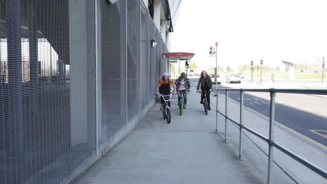 vídeos de stock, filmes e b-roll de ciclistas de bmx das mulheres que ciclagem abaixo da rampa fora de um edifício industrial moderno - termo esportivo