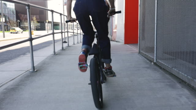 Women BMX riders cycling down ramp outside industrial building