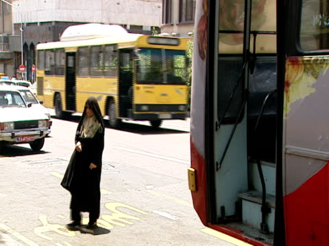 ms women board a bus at a bus stop on a busy city ctreet / tehran iran - medium group of objects stock videos & royalty-free footage