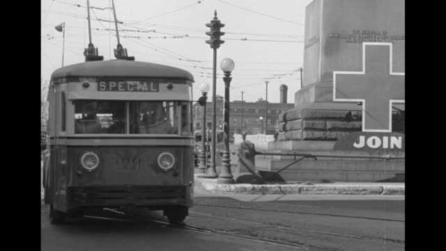 vídeos de stock, filmes e b-roll de women board streetcar as men stand nearby / streetcar approaches passes as it moves on track it passes a sign urging people to join the red cross /... - bonde