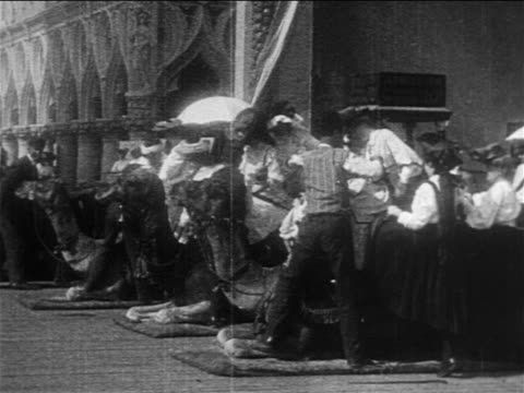 b/w 1905 women boarding camels in amusement park ride / coney island / documentary - coney island brooklyn stock videos & royalty-free footage