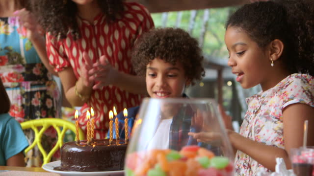 MEDIUM HANDHELD women, boy and girl watch boy blow out candles on birthday cake and cheer