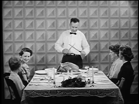 B/W 1945 women + boy watching as man standing at head of table sharpens carving knife to cut turkey