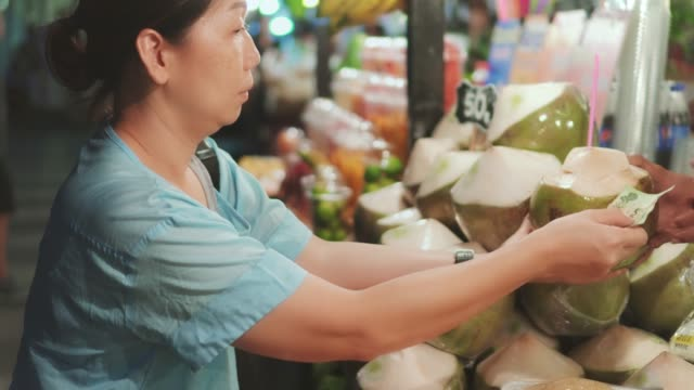 women buying coconut on street food ,thailand - banknote stock videos & royalty-free footage