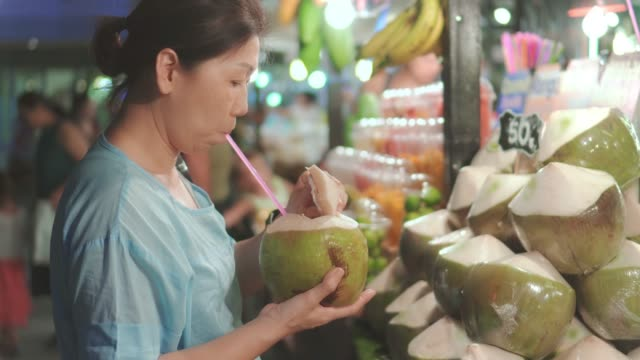 vídeos de stock e filmes b-roll de women buying coconut on street food ,thailand - banca de mercado