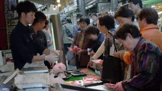 vidéos et rushes de women buying fresh seafood at tsukiji market - marché établissement commercial