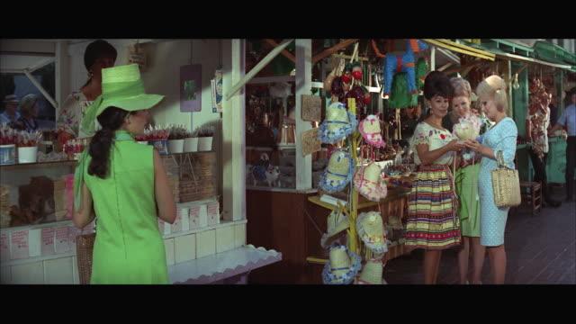 vídeos de stock, filmes e b-roll de 1967 ms women buying hats in mexican gift shop. - formato letterbox