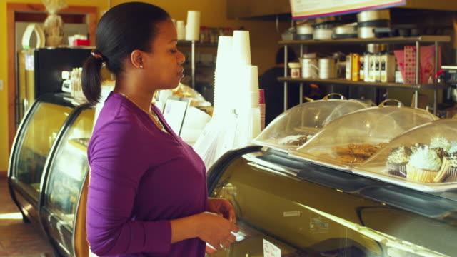 ms tu women buying muffin in coffee shop / manchester, vermont, usa - skåp med glasdörrar bildbanksvideor och videomaterial från bakom kulisserna