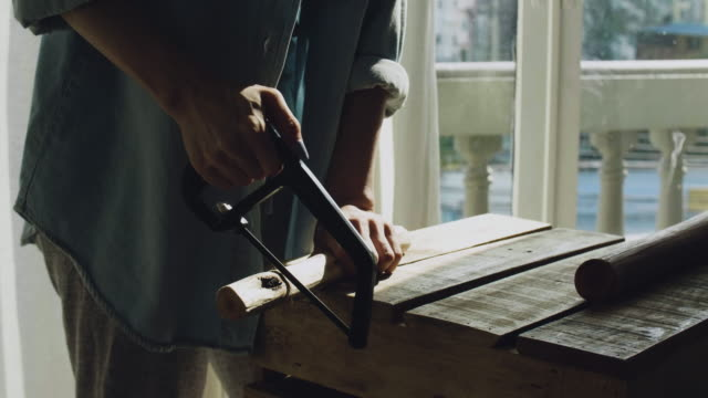 women carpenter sawing wood with hand saw - hand saw stock videos and b-roll footage
