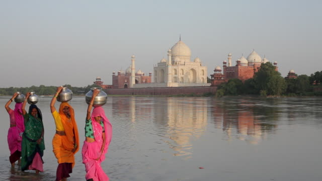women carry jugs of water near the jumna yamuna river near the taj mahal. - taj mahal stock videos and b-roll footage