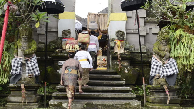 ms women carry offerings on her head and going in colorful decorated pura desa temple for ceremony audio / ubud, bali, indonesia, asia - furzen stock-videos und b-roll-filmmaterial