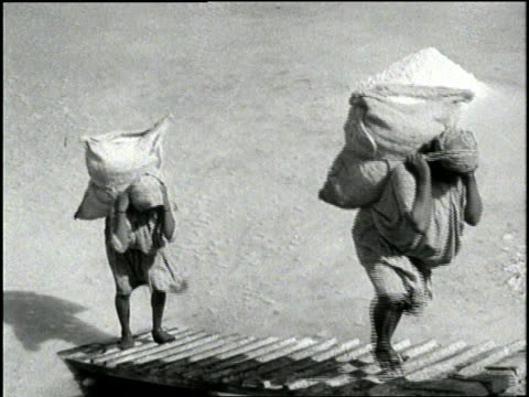 women carry sacks of sea salt on their backs and dump them in piles in colombia south america - colombia stock videos & royalty-free footage