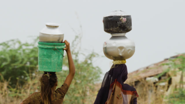 women carry water containers on their heads, india. - 運ぶ点の映像素材/bロール